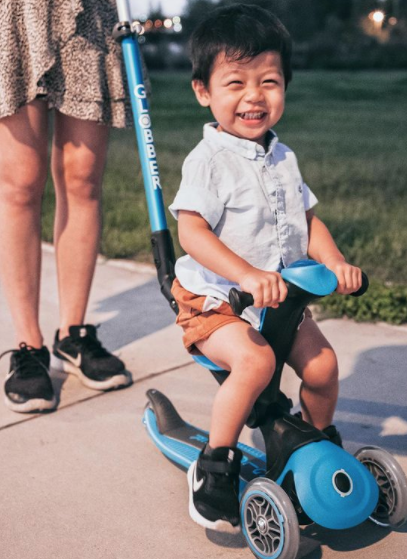 Kid enjoys his Globber GO UP DELUXE sky blue scooter with seat